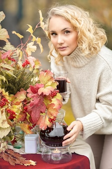 Herfst. het meisje schenkt een fruitige rode thee in de beker. een tafel aan de oever van het meer is versierd met een boeket herfstbladeren. thee drinken vruchtenthee met citroen, appels
