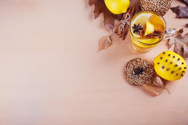 Herfst hete thee met citroen en kruiden in glazen beker. gezonde thee met koekjes, walnoten en bladeren rond. herfst concept