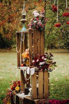 Herfst huwelijksceremonie op straat op het groene gazon.decoratie met bogen van verse bloemen voor de ceremonie.