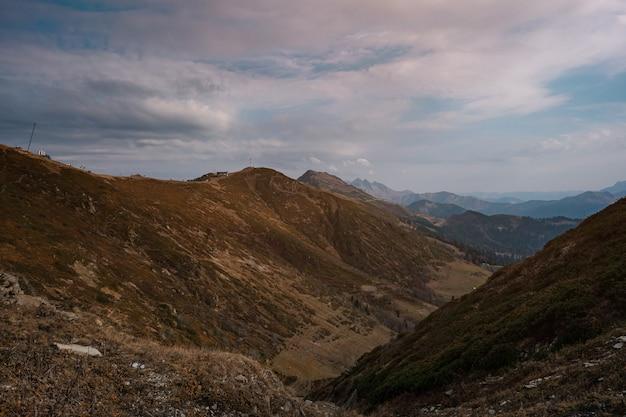Herfst in de noord-kaukasus, skigebied rosa khutor in het laagseizoen. rusland, sotsji. vintage toning. reizen achtergrond. dramatische hemel, zonsondergangtijd, mooie zware wolken.