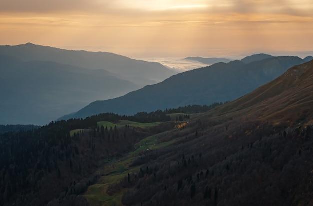 Herfst in de noord-kaukasus, skigebied rosa khutor in het laagseizoen. rusland, sotsji. vintage toning. reizen achtergrond. landschap met zonlicht schijnt door oranje wolken en mist.