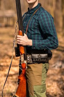 Herfst jachtseizoen. mensenjager met een kanon. jagen in het bos