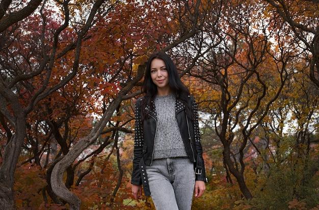 Herfst jonge blanke vrouw met een zwart leren jack en een grijze trui en spijkerbroek in het herfstpark. warm weer.
