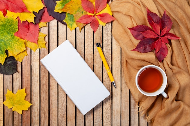 Herfst kaart voor uw ontwerp, bovenaanzicht met copyspace. hete thee, wit notitieboek, gele pen, oranje plaid, houten bladeren met lege ruimte voor tekst. plat leggen. seizoensgebonden relax