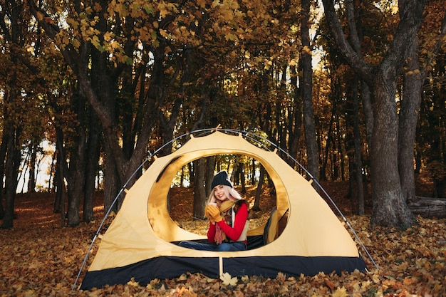 Herfst kamperen. dame zitten in tent met mok, genieten van tijd in herfst bos, glimlachend.