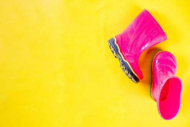 Herfst kinderen doek concept, fel roze rubberen laarzen voor regen