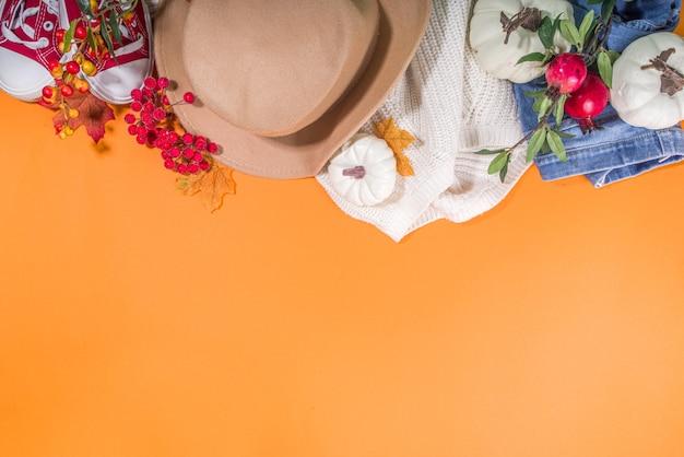 Herfst kleding gezellige mode concept. warme witte trui, jeans, sneakers met herfstdecor op een feloranje achtergrond bovenaanzicht flatlay