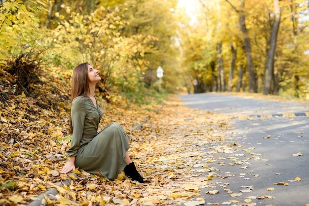 Herfst kleuren. mooie vrouw in jas poseren in bos langs de weg