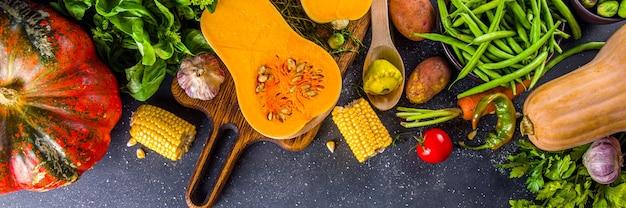 Herfst koken achtergrond. biologische herfstoogstgroenten, rauwe veganistische ingrediënten voor het koken van traditionele thanksgiving en herfstvoedsel op donkere achtergrond, bovenaanzicht