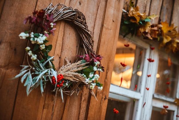 Herfst krans en pompoenen op houten rustieke achtergrond.