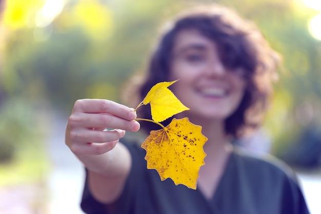 Herfst - lachend meisje houdt een geel blad vast