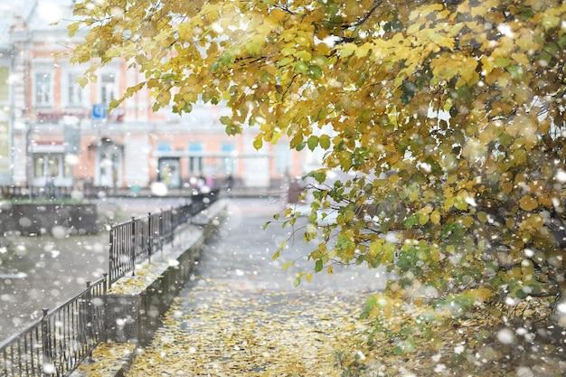 Herfst landschap. de bladeren vliegen van de bomen in de stad. herfst in de stad op kleine straat langs gesmede hekken