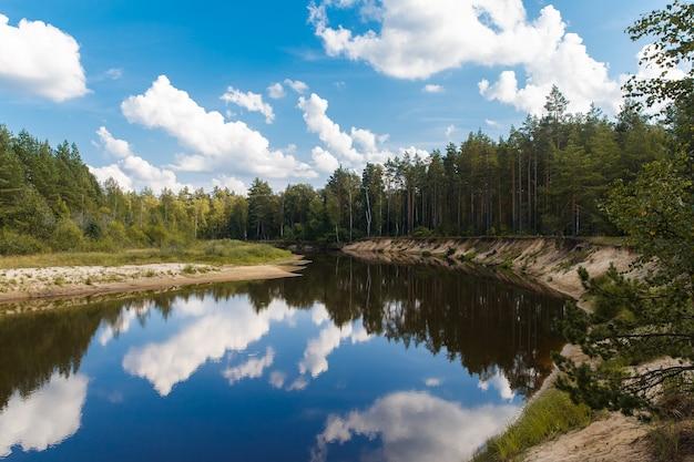 Herfst landschap. de rivier stroomt door het bos, blauwe lucht met wolken.