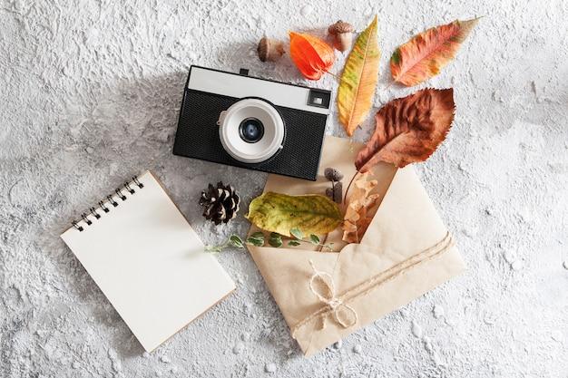 Herfst lay-out met vintage camera, envelop, leeg notitieboekje en gevallen bladeren. bovenaanzicht compositie