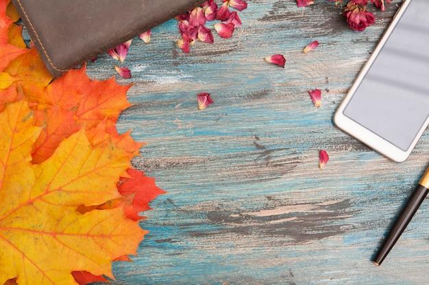 Herfst layout met geeloranje bladeren, pen en notitieboek, droge rozenblaadjes. kopieer ruimte