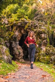 Herfst levensstijl blonde blanke meisje in een rode trui en spijkerbroek en met hoge hakken genieten van de natuur in een park met een natuurlijke grot