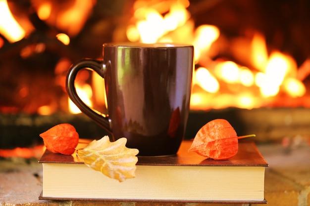 Herfst lezen. boeken in de herfst. boek en thee op een open haard