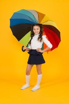 Herfst look. klein schoolkind met kleurrijke paraplu voor herfstweer op gele achtergrond. klein meisje dat op herfstdag of 1 september naar school gaat. terug naar school in de herfst.