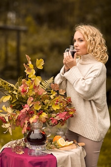 Herfst. meisje dat hete fruit rode thee in koppen drinkt. een tafel aan de oever van het meer is versierd met een boeket herfstbladeren. thee drinken vruchtenthee met citroen, appels