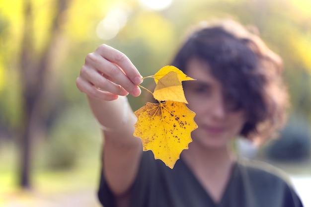Herfst - meisje houdt een geel blad vast