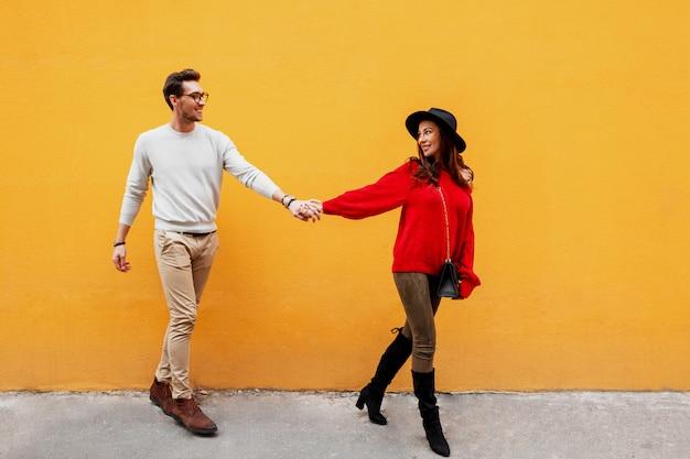 Herfst mode beeld van elegante stijlvolle paar verliefd hand in hand en kijken met plezier naar elkaar.