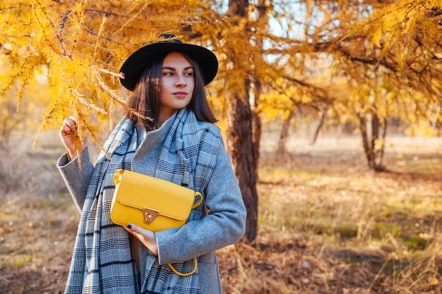 Herfst mode. jonge vrouw die modieuze uitrusting draagt en beurs in openlucht houdt