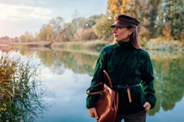 Herfst mode. jonge vrouw die modieuze uitrusting draagt en handtas in openlucht houdt
