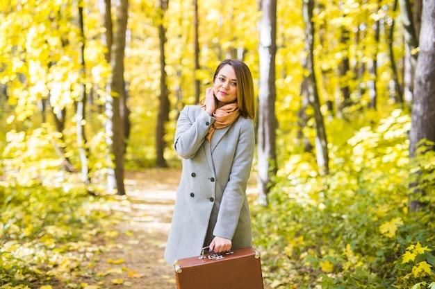 Herfst, mode, mensen concept - vrouw met bruine retro koffer wandelen door de herfst park en glimlachen.
