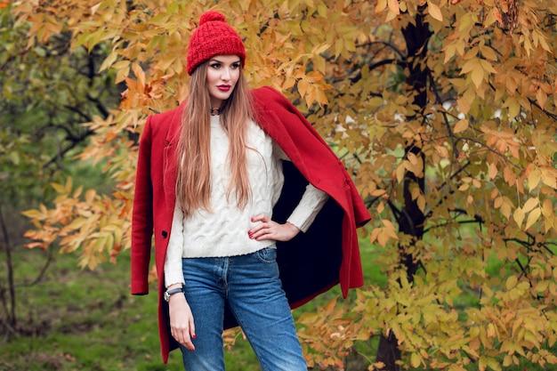 Herfst mode portret van blonde vrouw in rode stijlvolle jas en gebreide muts wandelen in het park.
