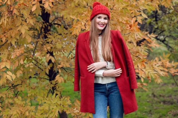 Herfst mode portret van gelukkige blonde vrouw in rode stijlvolle jas en gebreide muts wandelen in het park.