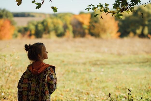 Herfst natuurpark. leuk meisje in warme jas genieten van zonnige dag. vervagen kopieer de ruimte.