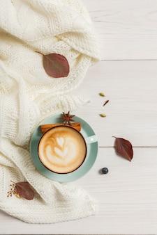 Herfst ochtend samenstelling. blauwe koffiekop met warme schuimende cappuccino bovenaanzicht, kruidnagel, kaneel en warme trui op wit hout. val pittige dranken concept