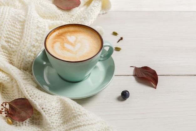 Herfst ochtend samenstelling. blauwe koffiekop met warme schuimende cappuccino, kruidnagel, kaneel en warme trui op wit hout. val pittige dranken concept