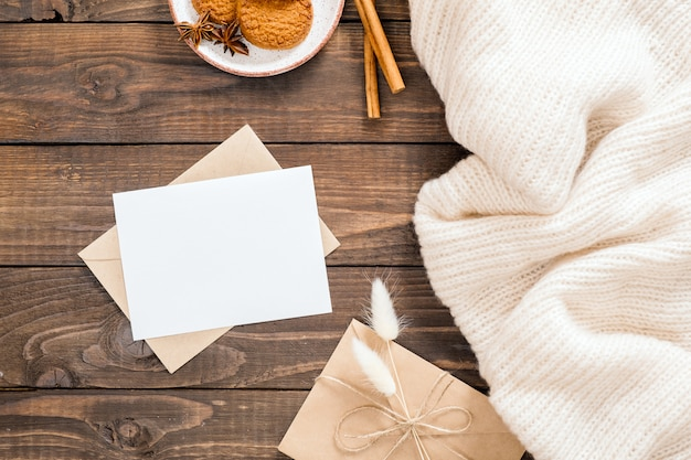 Herfst of winter flatlay samenstelling met witte wollen plaid, lege witte kaart, envelop, kaneelstokjes, koekjes, droge bloemen