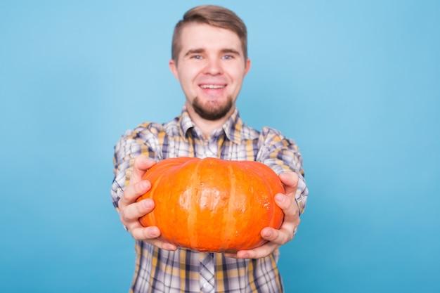 Herfst oogst en landbouw concept glimlachende man met pompoenen over blauwe achtergrond