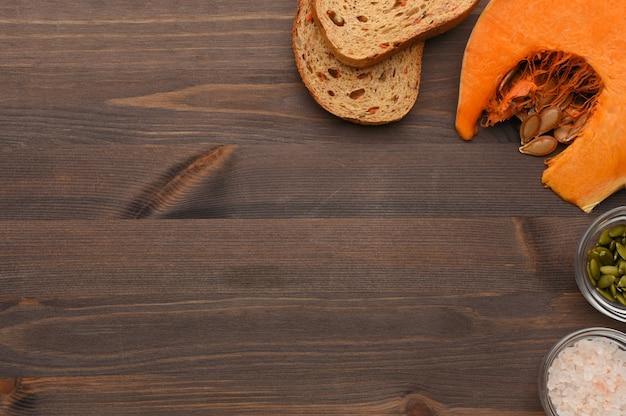 Herfst plantaardige houten achtergrond met plak van rijpe pompoen, wortel biologisch brood, zaden en roze hawaii zout grens.