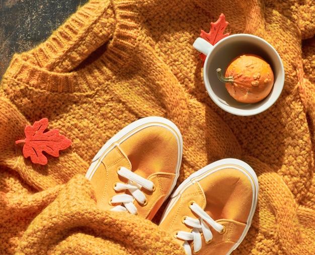 Herfst plat lag met gele trui, decoratieve pompoen in theekop en herfstbladeren