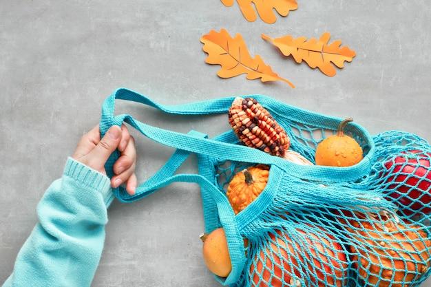 Herfst plat lag met turquoise string tas met oranje pompoenen, top vie op grijze steen