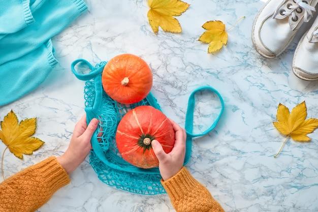 Herfst plat lag met vrouwelijke handen oranje pompoen in turquoise string tas. bovenaanzicht op witte marmeren achtergrond met witte schoenen, trui en gele bladeren.