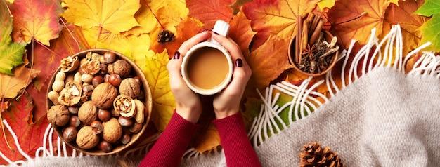 Herfst plat lag. vrouwelijke handen met kopje koffie, beige plaid, houten kom met noten