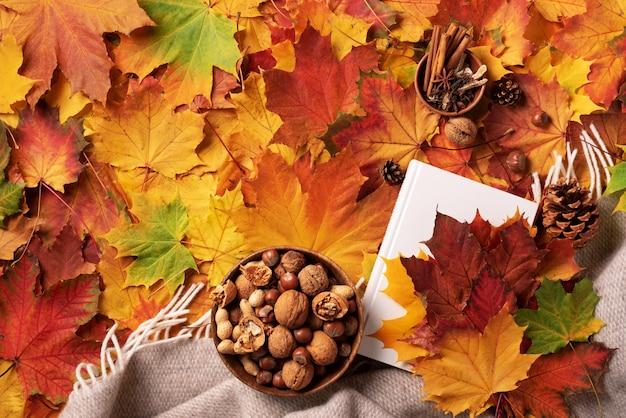 Herfst plat lag. wit boek, houten kom van noten, koffiekop, kegel, kaneel over beige plaid en kleurrijke bladerenachtergrond.