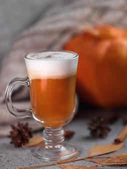 Herfst pompoen latte glas. een warm drankje en een gebreide sjaal op de grijze tafel.