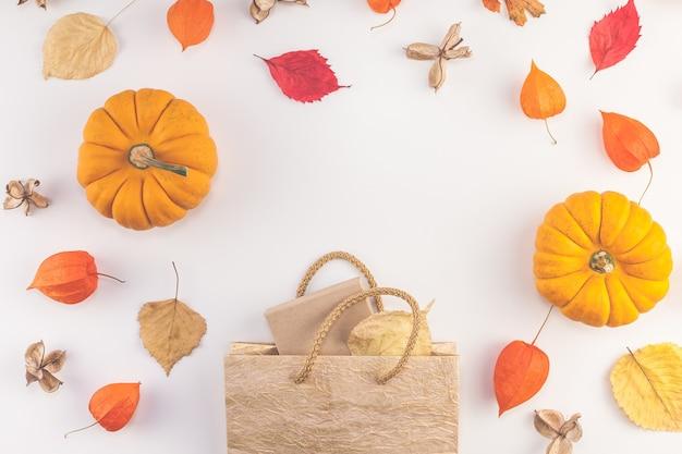 Herfst pompoenen, gedroogde oranje bloemen en bladeren