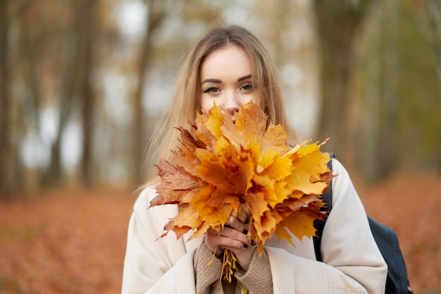 Herfst portret. mooie stijlvolle blonde meisje met boeket van esdoorn bladeren in de buurt van gezicht dragen van trendy herfst jas poseren in herfst park.
