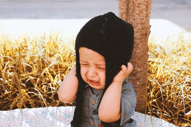 Herfst portret van 2-3 jaar oud kind huilen in de tuin. herfst seizoen. ongelukkig gemengd ras jongetje in gebreide muts