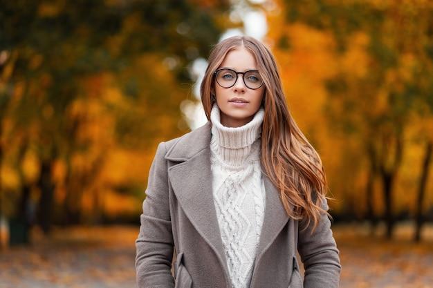 Herfst portret van een aantrekkelijke jonge vrouw in stijlvolle glazen in een gebreide modieuze witte trui in een elegante jas in een park op een achtergrond van bomen met oranje bladeren. meisje wandelingen in het bos