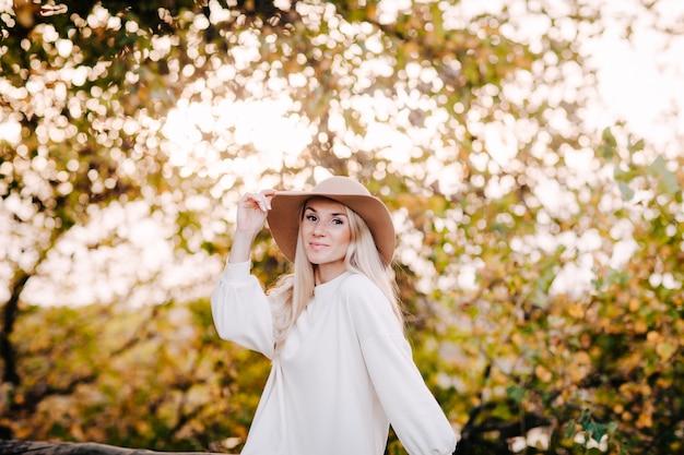 Herfst portret van een jonge blonde vrouw in een beige hoed en witte jurk