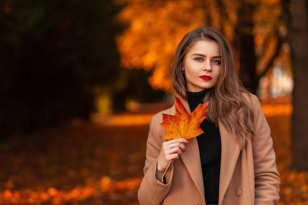 Herfst portret van een mooi jong meisje met een gekleurd rood-oranje esdoornblad in een modieuze beige jas met een trui loopt in het park met gebladerte. plaats voor tekst, kopieer ruimte