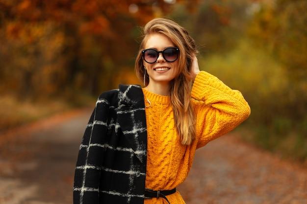 Herfst portret van een mooi jong meisje met een kaukasisch lachend gezicht in een vintage gebreide trui en een zwarte jas met zonnebril wandelingen in de natuur. vrouwelijk model in herfstdag met geel blad
