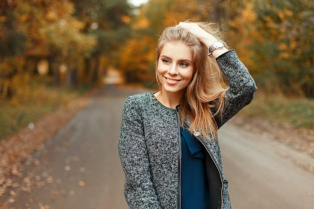 Herfst portret van een mooie gelukkige vrouw met een glimlach in modieuze kleding in het park